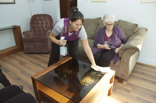 cleaner helping senior person